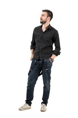 Serious young man with hands in pocket looking up. Full body length portrait isolated over white background.