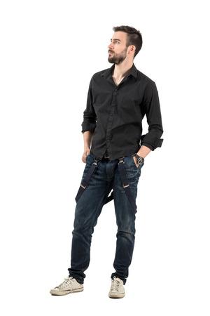 Ernster junger Mann mit den Händen in der Tasche nach oben. Ganzkörper-Portrait über weißem Hintergrund.