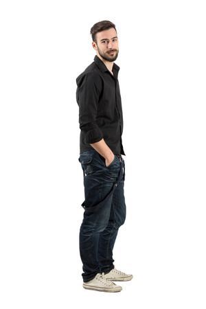 man side: Relaxed young man side view looking at camera. Full body length portrait isolated over white background.