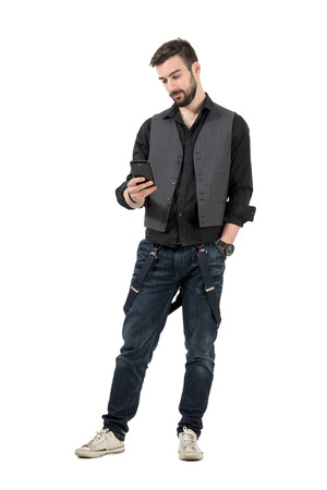 rolled up sleeves: Young trendy man reading message on his cellphone. Full body length portrait isolated over white background.