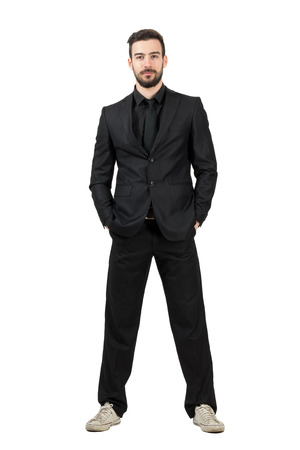 Bearded young businessman in white sneakers looking at camera. Full body length portrait isolated over white studio background.