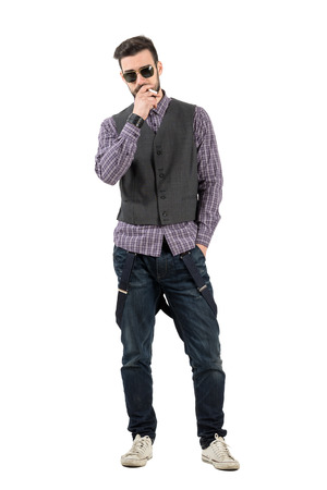 Confident young man with sunglasses smoking cigarette looking at camera.  Full body length portrait isolated over white background. photo
