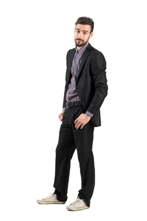 indifferent: Young bearded man in business suit and white sneakers indifferent looking at camera. Full body length portrait isolated over white background.