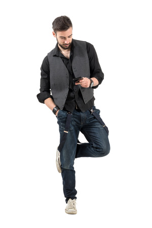 Young bearded guy scratching rubbing legs while on smartphone. Full body length portrait isolated over white background.
