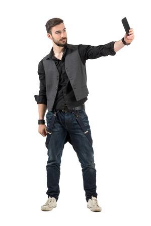 Jong lachend bebaarde hipster nemen selfie vanuit hoge hoek. Full body lengte portret geïsoleerd op een witte achtergrond.
