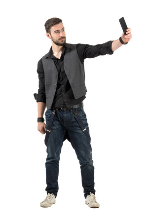 Young smiling bearded hipster taking selfie from high angle. Full body length portrait isolated over white background. photo
