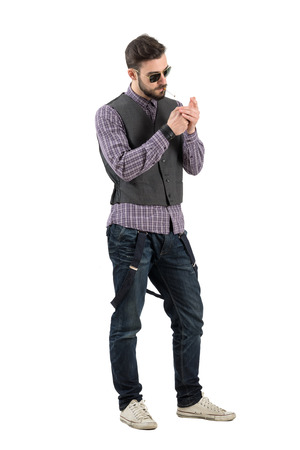 joven fumando: Fresco hombre de moda relajada iluminando cigarrillo. Carrocería completa longitud retrato aislado sobre fondo blanco. Foto de archivo