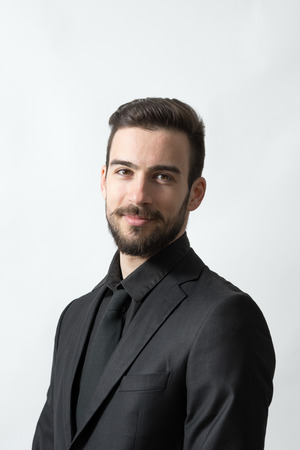 gray suit: Smiling happy young bearded elegant man in black suit. Head and shoulders portrait over grey studio background.