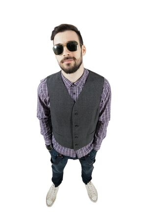 wide angle lens: Confident young relaxed hipster with hands in pockets. High view wide angle lens portrait isolated over white background. Stock Photo
