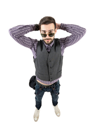 wide angle lens: Funny young relaxed hipster with hands behind head. High view wide angle lens portrait isolated over white background.