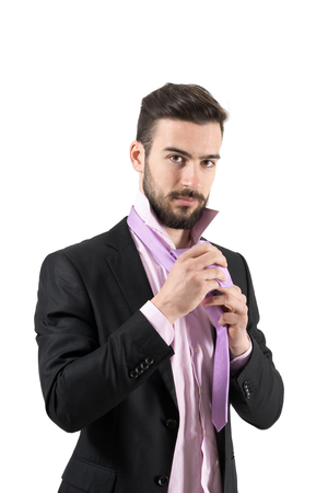 vistiendose: Joven barbudo hombre de negocios que ata la corbata nudo vestirse. Retrato aislado sobre fondo blanco. Foto de archivo