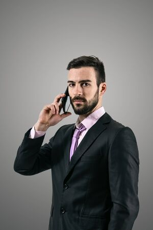 Dramatic high contrast portrait of serious confident business man talking on the cellphone over dark gray background with vignette. photo
