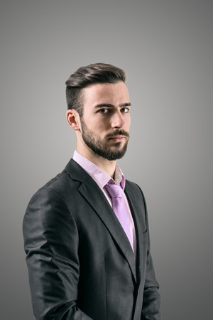 men in suit: Portrait of mysterious young bearded man suspiciously looking at camera over dark grey background with retro vignette effect. Stock Photo