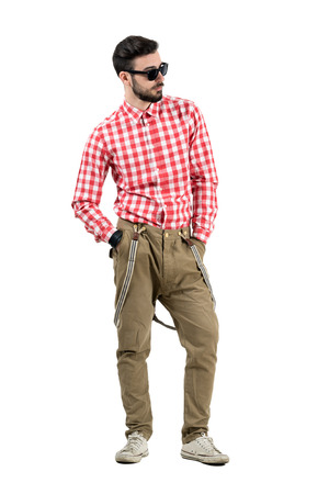 hands on pocket: Relaxed casual hipster with hands in pocket looking away. Full body length portrait isolated over white background. Stock Photo