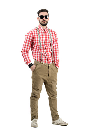 Cool relaxed young hipster with sunglasses looking at camera. Full body length portrait isolated over white background. photo