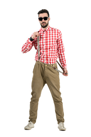 Cool young bearded hipster putting on suspenders. Full body length portrait isolated over white background.