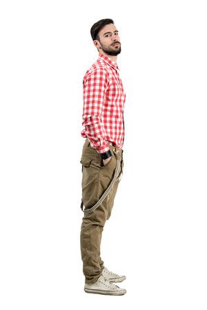 completos: Vista lateral joven confía inconformista barbudo con las manos en los bolsillos. La longitud del cuerpo completo retrato aislado más de fondo blanco Foto de archivo