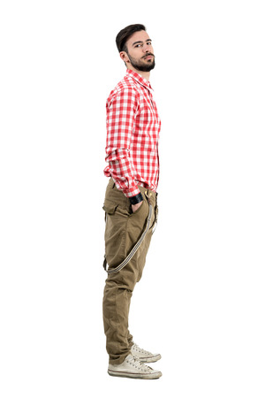 Young confident bearded hipster side view with hands in pockets. Full body length portrait isolated over white background