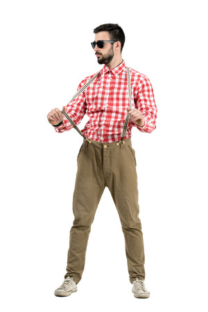 Young bearded hipster pulling suspenders looking away. Full body length portrait isolated over white background. photo