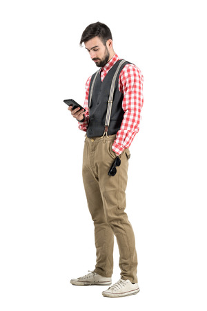 length: Relaxed young man in retro clothes typing message on smartphone.  Full body length portrait isolated over white studio background.