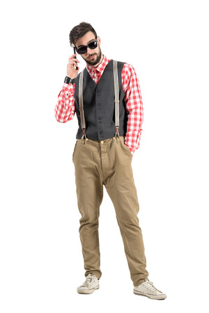 Cool young bearded hipster talking on the mobile phone. Full body length portrait isolated over white studio background. photo