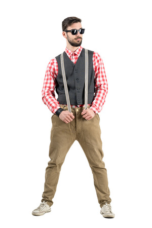 Confident young hipster holding suspenders looking away. Full body length portrait isolated over white studio background. photo