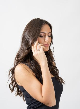 voluptuosa: Bronceada belleza morena de pelo largo hablando por el móvil mirando hacia abajo. Retrato sobre fondo gris de estudio.