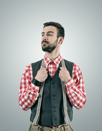 raised eyebrow: Desaturated portrait of standing young hipster model looking away with raised eyebrow while holding his pants suspenders. Stock Photo
