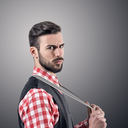 Dramatic portrait of angry bearded hipster with intense look at camera over dark gray studio background with vignette.