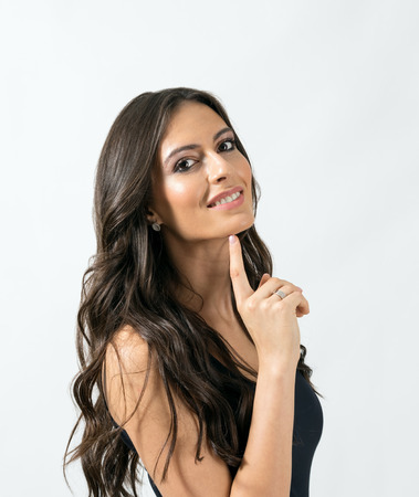 spanish girl: Attractive tanned brunette woman posing at camera while touching chin with tip of her finger. Portrait over gray studio background.