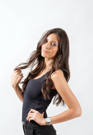 hispanic girls: Gorgeous Latin beauty twirling wisp of her healthy dark long hair. Portrait over gray studio background.