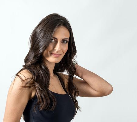 Brunette abbronzato bellezza con mano che tocca i suoi capelli ondulati lunghi. Ritratto su sfondo grigio studio.
