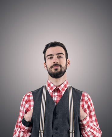 Desaturated portrait of young bearded hipster with hands pushed in his vest over dark gray studio background with vignette.