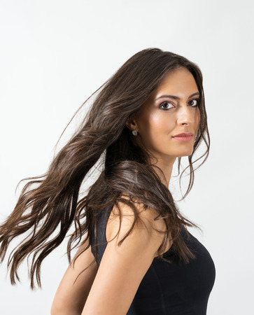 gray hairs: Gorgeous exotic tanned beauty with frozen motion of her long flowing hair. Portrait over gray studio background. Stock Photo
