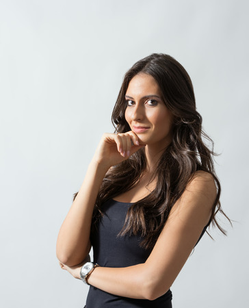 Portrait of tanned Latin woman with chin resting on her hand over gray studio background.