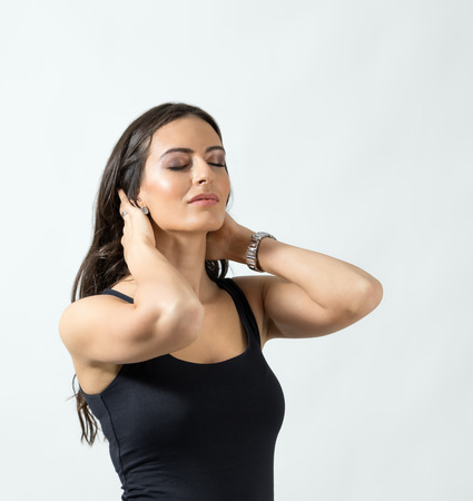 Portrait of a woman with closed eyes touching her neck. Studio portrait over the gray background. Stock Photo