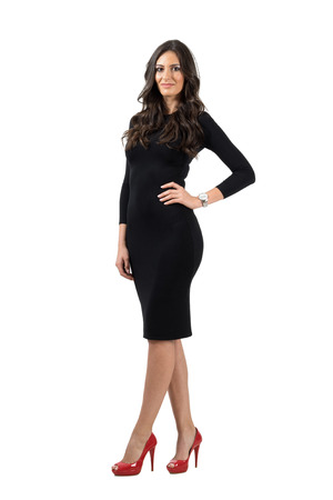 little black dress: Elegant young woman in short little dress looking at camera. Full body length portrait isolated over white studio background.