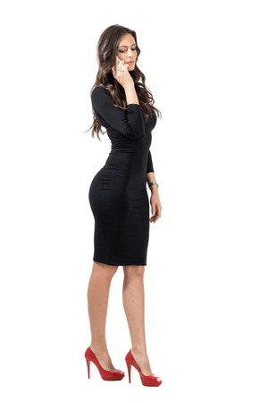 phone isolated: Elegant Hispanic business woman looking down while talking on the smart phone. Full body length portrait isolated over white studio background.