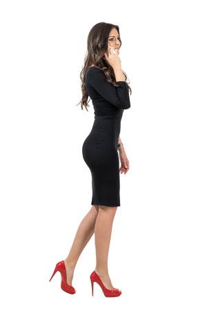 Elegant business woman walking while talking on the mobile phone looking away. Full body length portrait isolated over white studio background.