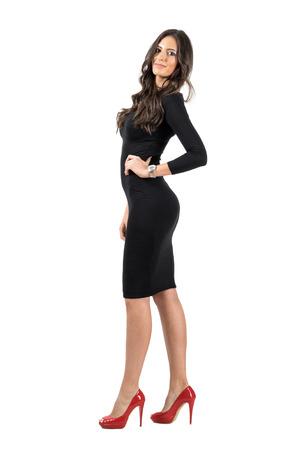 cuerpo completo: Mujer de negocios joven del Latino en vestido corto negro posando a la cámara. Todo el cuerpo retrato de cuerpo entero aisladas sobre fondo blanco de estudio.