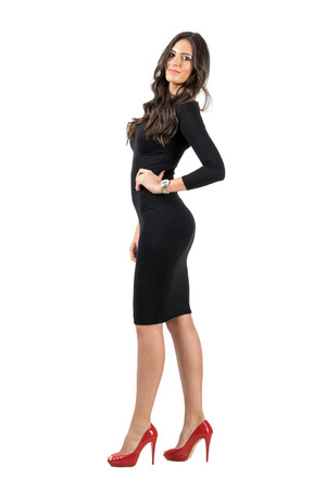 from side: Young Latino business woman in short black dress posing at camera. Full body length portrait isolated over white studio background.