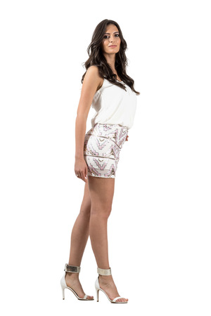 Glamour vogue Hispanic woman in short mini skirt posing looking at camera.  Full body length portrait isolated over white studio background. Stock Photo
