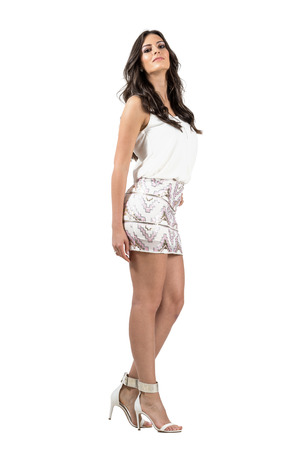 miniskirt: Passionate Latin beauty in vogue nightlife dress with head lean back.  Full body length portrait isolated over white studio background.