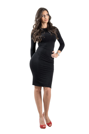 Young elegant lady in black dress looking away with hand on her hip. Full body length portrait isolated over white studio background.