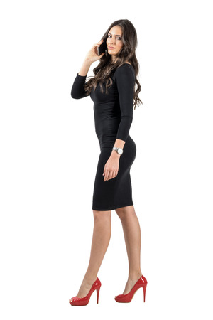 woman dress: Side view of walking elegant business woman on the phone.  Full body length portrait isolated over white studio background.