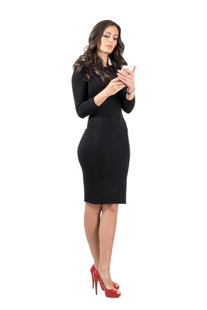 serious: Beautiful business woman in elegant black dress typing on her smartphone. Full body length portrait isolated over white studio background. Stock Photo