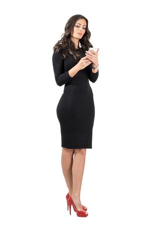 Schöne Business-Frau im eleganten schwarzen Kleid die Eingabe auf Ihrem Smartphone. Ganzkörper-Länge Portrait über weißem Hintergrund Studio isoliert.