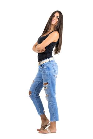 completos: feliz mujer latina joven y sonriente con los brazos cruzados mirando a la cámara. Vista lateral. la longitud del cuerpo Retrato completo aislado sobre fondo blanco del estudio.