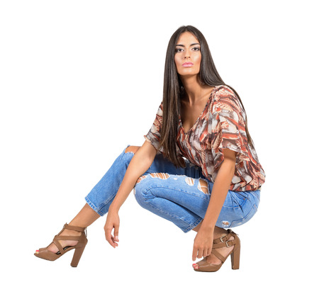 sit studio: Confident serious young Latin woman in casual clothes crouched pose looking at camera.  Full body length portrait isolated over white studio background. Stock Photo
