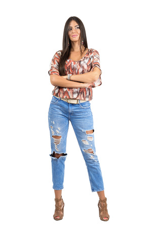 portrait studio: Young hispanic long straight hair beauty with crossed hands looking away.  Full body length portrait isolated over white studio background. Stock Photo